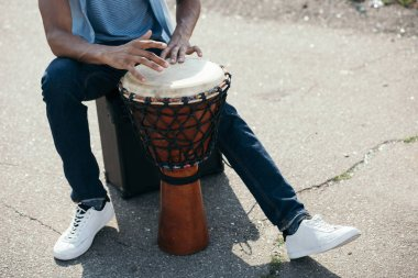 Cropped view of African american man with djembe performing on street