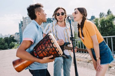 Team of young friends with musical instruments singing by microphone in urban environment