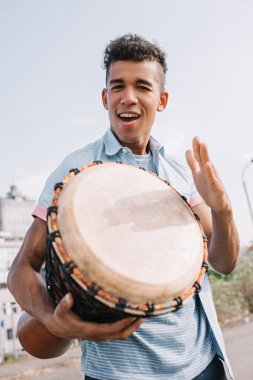 Young and happy african american street musician with djembe performing on sunny city street