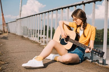 Young woman with guitar sitting on ground and performing on street