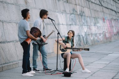 Team of young friends playing guitars and djembe in urban environment