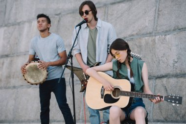 Young and happy male and female street musicians playing guitars and djembe in city