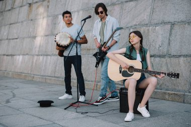 Young girl and multiracial men with musical instruments performing on sunny city street