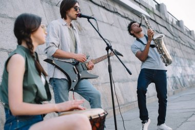 Street musicians band performing with guitar, drum and saxophone on sunny city street