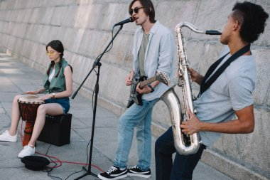Team of young friends musicians playing and singing in urban environment