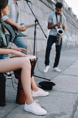 Talented street musicians with guitar, drum and saxophone performing in city