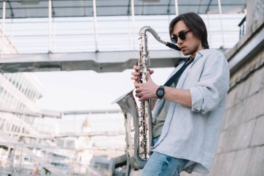 Young man in sunglasses adjusting saxophone on sunny city street