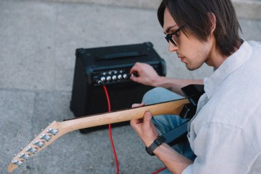 Busker adjusting guitar amplifier while performing on sunny city street