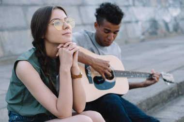 Dreamy girl listening to African american man playing guitar in city