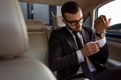 handsome businessman buttoning cuff in car