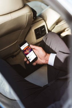 cropped image of businessman holding smartphone with loaded soundcloud page in car