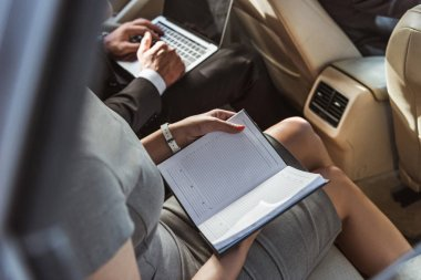 cropped image businessman and assistant working in car with laptop and notebook