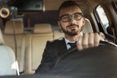 Fotografie handsome cheerful driver in suit driving car