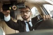 Fotografia driver bel vestito guida auto e fissaggio specchio