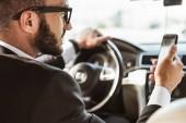 Fotografie hezký ovladač v obleku řídit auto a držení smartphone