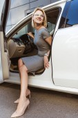 Photo attractive businesswoman in dress and high heels going out from car