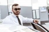 Fényképek szép vezető napszemüveg közelében autó állt, és nézte a kamera