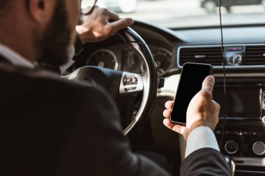 cropped image of driver in suit driving car and holding smartphone