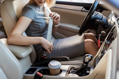 cropped image of businesswoman fastening safety belt in car