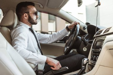 side view of handsome driver in sunglasses driving auto