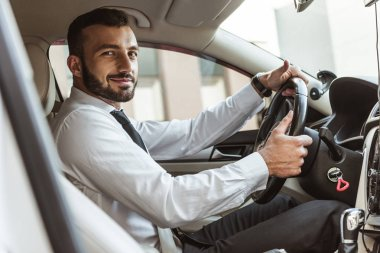 smiling handsome driver holding steering wheel and looking at camera in car
