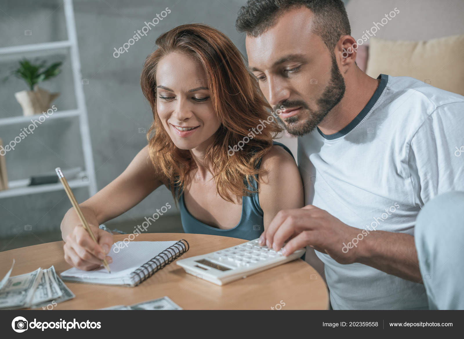 couple planning family budget notebook calculator living room