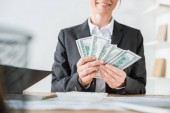 Fotografie cropped image of smiling financier counting money in office