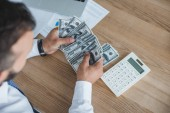 Fotografie cropped image of financier counting cash with calculator in office