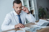 pensive business adviser counting money with calculator in office