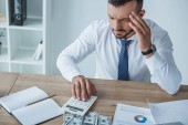 Fotografie pensive financier counting money with calculator in office and having headache