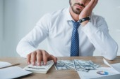 cropped image of tired financier counting money with calculator in office