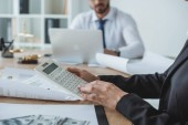 oříznutý obraz finančníků pomocí kalkulačky a přenosný počítač v kanceláři