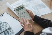 cropped image of financier using calculator in office