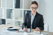 attractive financier working at table in office with calculator and clipboard