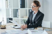 Fotografie attractive financier working with documents at table in office