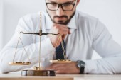 pensive business adviser looking at scales with precision weights in office