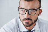 portrét pohledný podnikatel v brýlích při pohledu odtud izolované na bílém