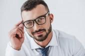 portrét usměvavý pohledný podnikatel v brýlích při pohledu na fotoaparát izolované na bílém