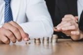 Fotografie cropped image of financiers stacking coins on table in office
