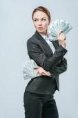 atraktivní finančník pózuje s dolarové bankovky a pohledu daleko izolované na šedá
