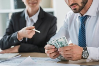 Cropped image of accountants sitting with dollars in office stock vector