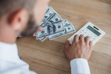 cropped image of business adviser counting dollars with calculator in office
