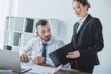 financier showing clipboard to colleague in office