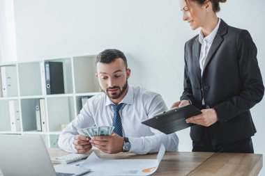 attractive financier showing clipboard to colleague in office
