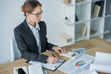 high angle view of financier working at table in office with calculator and clipboard