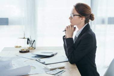 side view of financier sitting at table in office