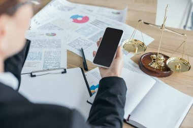cropped image of financier working at table in office and using smartphone