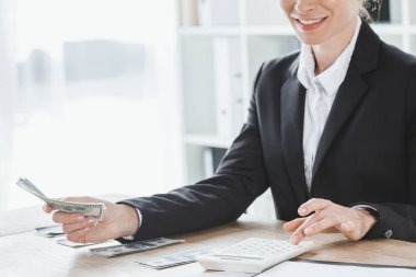 cropped image of financier calculating dollars in office
