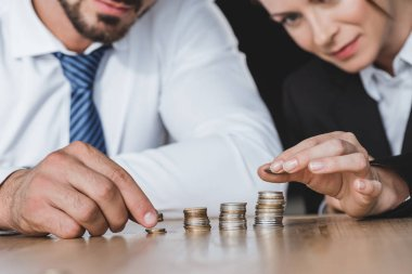 cropped image of business advisers stacking coins on table in office