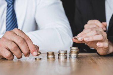 cropped image of financiers stacking coins on table in office